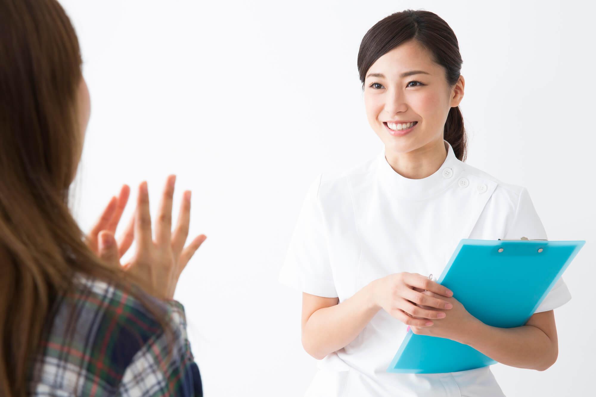 カウンセリングの方法や流れを女性クライアントに説明している女性カウンセラー