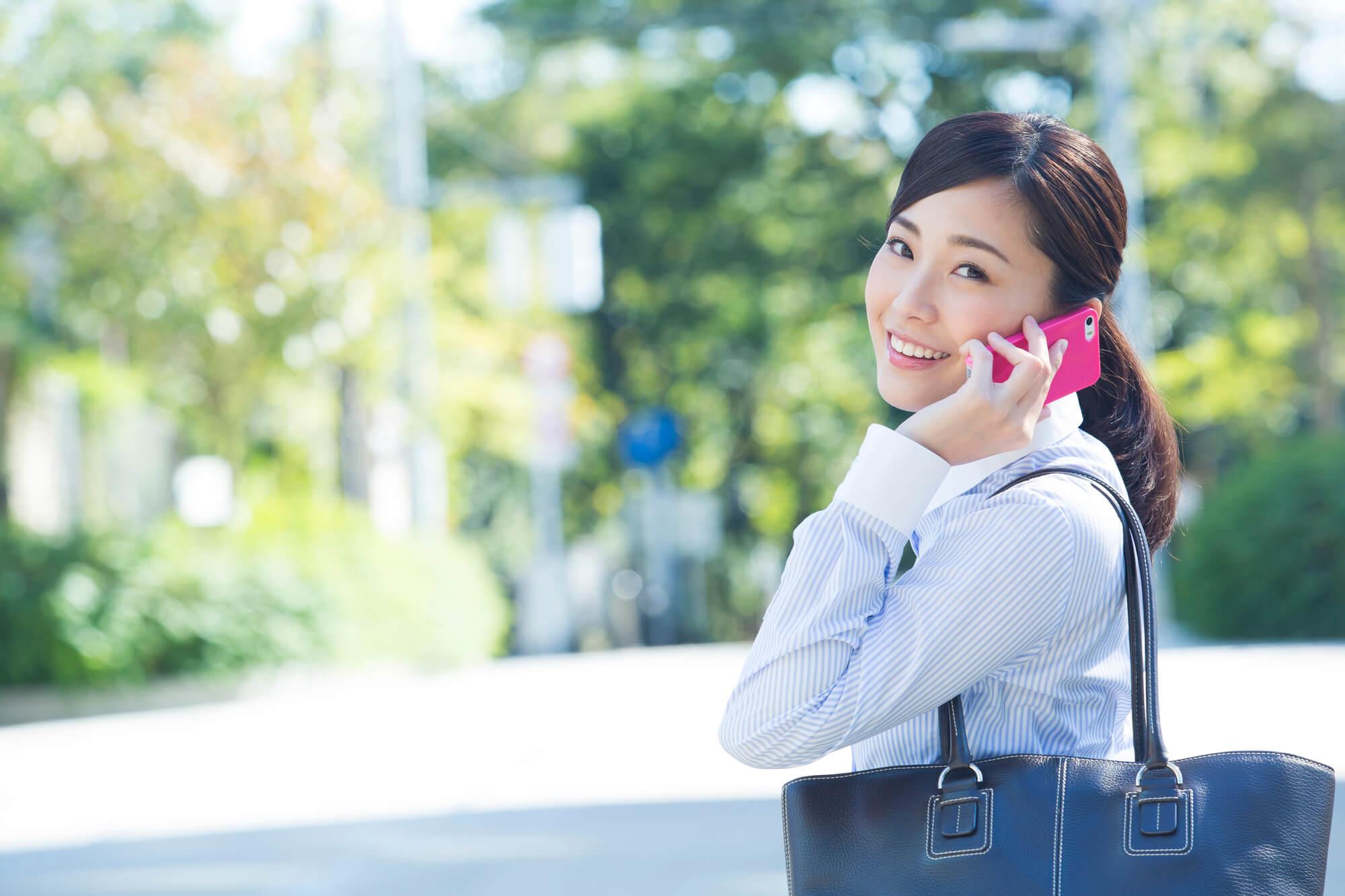 サービスの料金や相場を確認しているスーツの女性