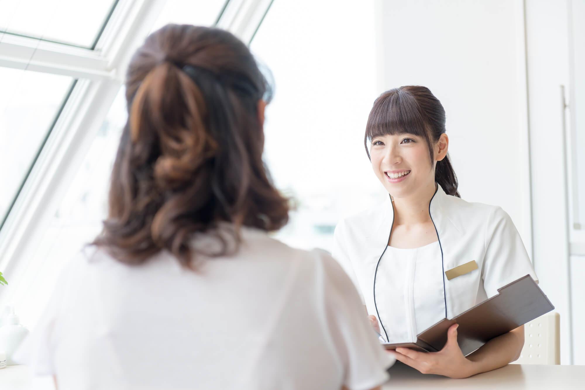 女性クライアントから質問を受け回答する女性カウンセラー