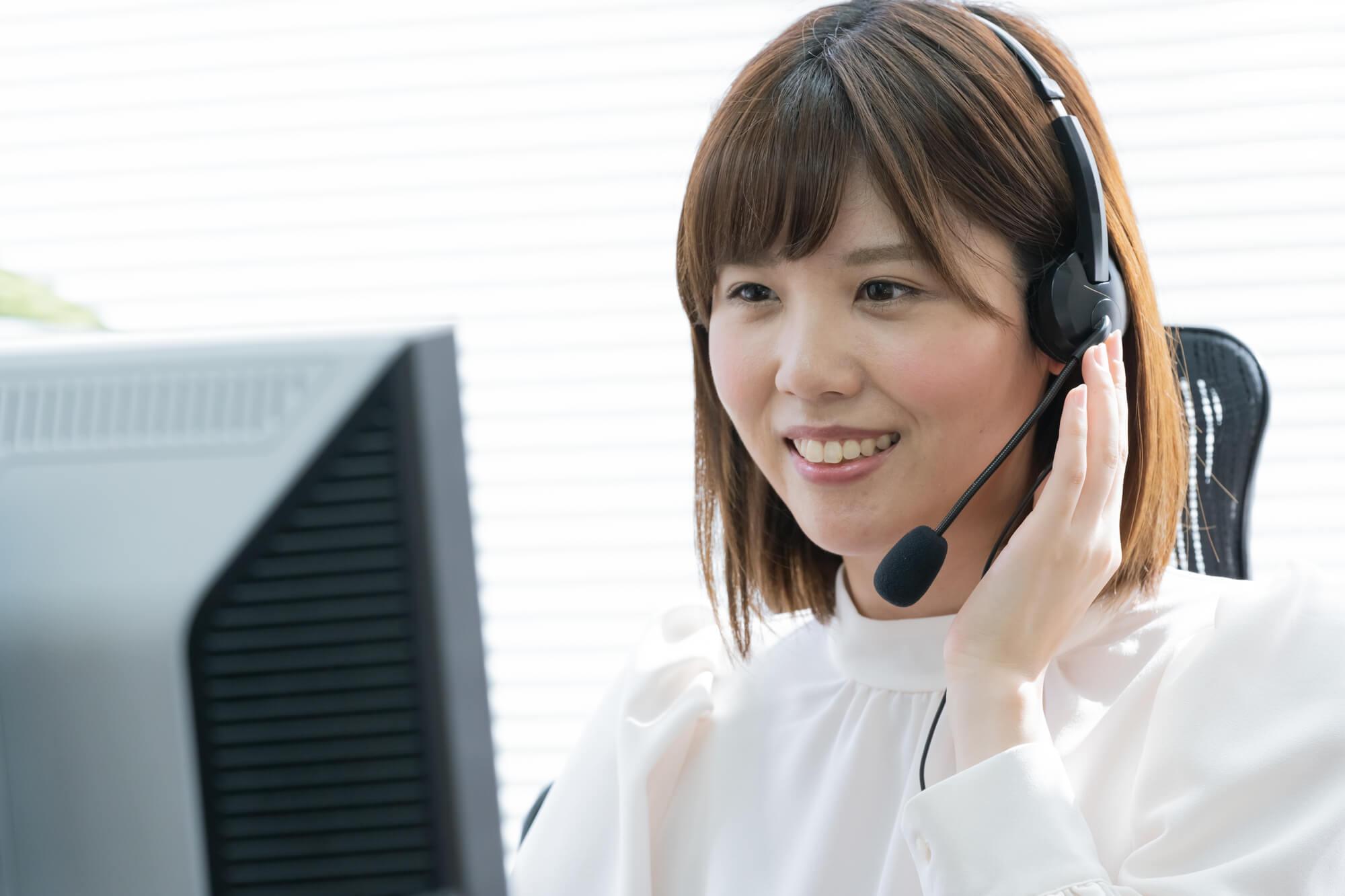 クライアントから電話で話を聞いている女性カウンセラー