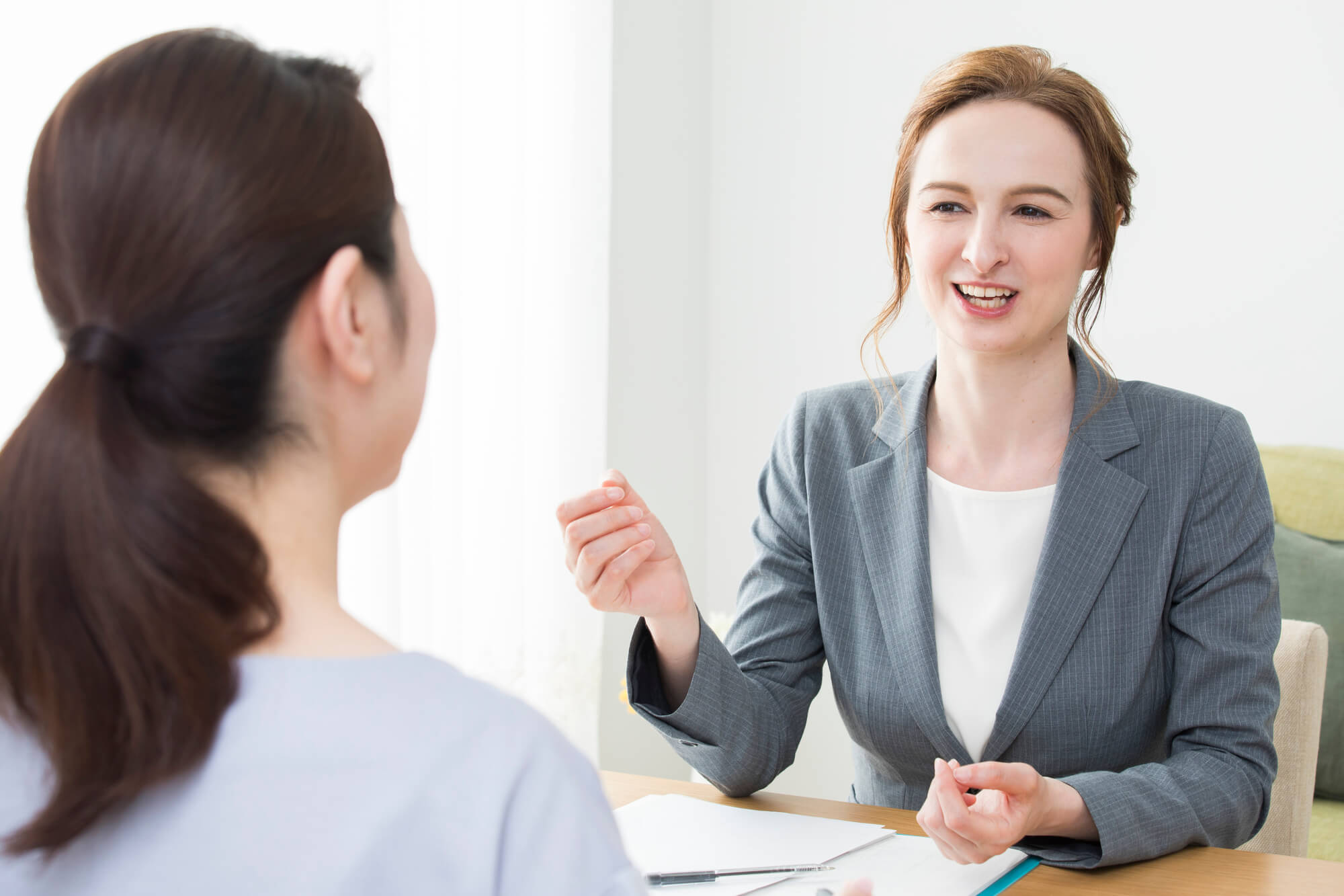 クライアントの相談を親身に聞いている外国人女性カウンセラー