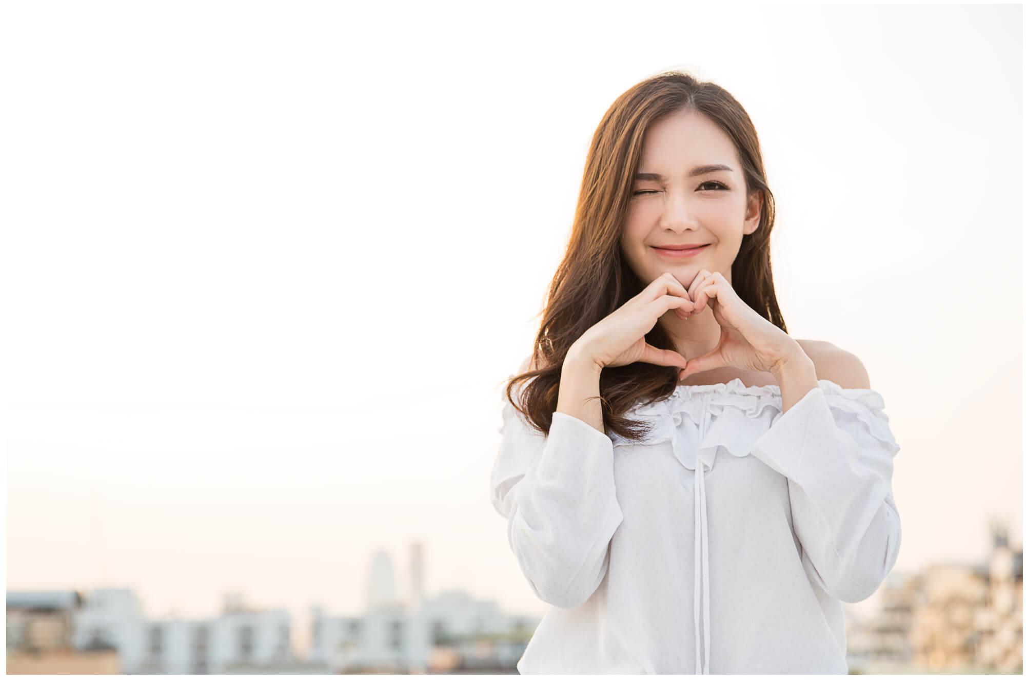 愛情をハートマークで表現する若い女性